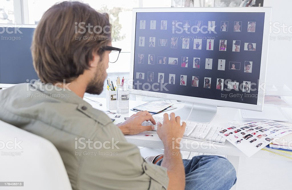 Photo editor looking at thumbnails on computer stock photo