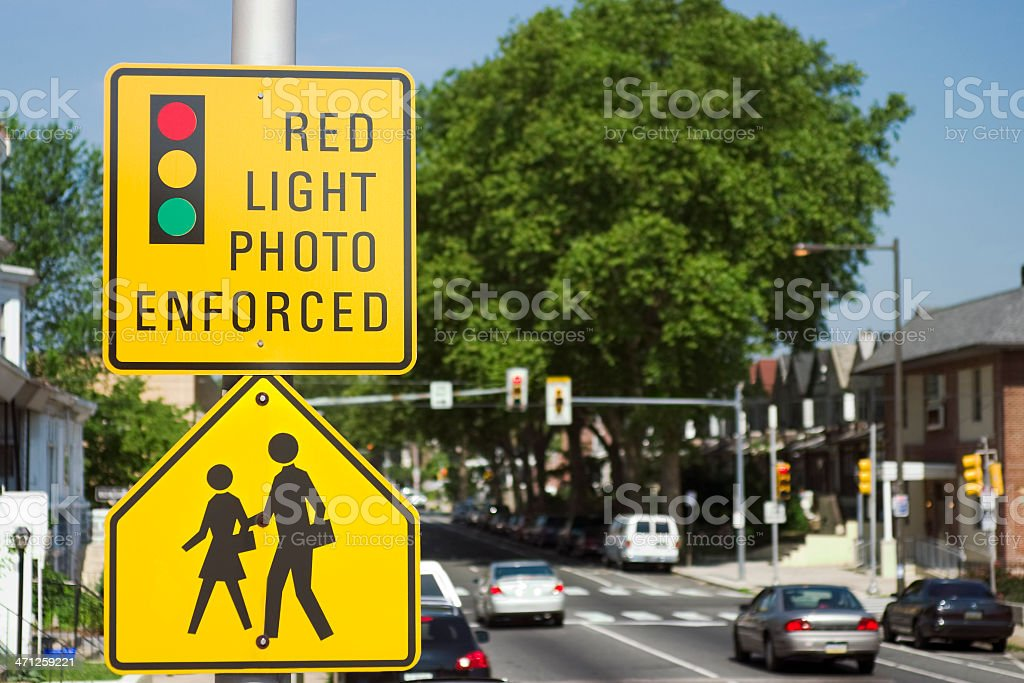 A photo enforced traffic light sign on a busy street stock photo