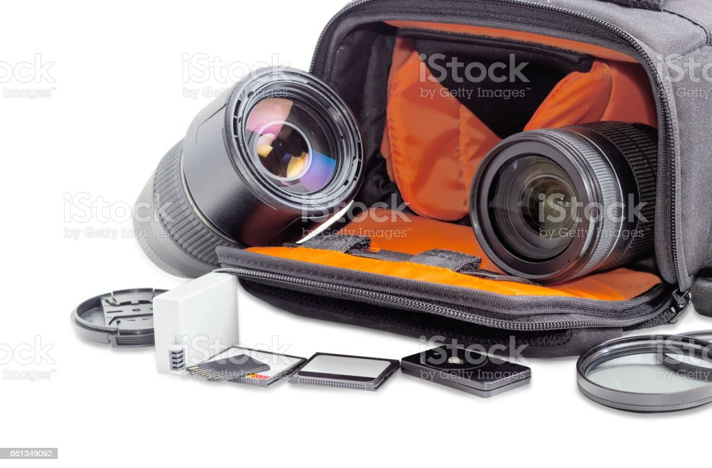 Photo lenses in open camera bag and some photo accessories stock photo