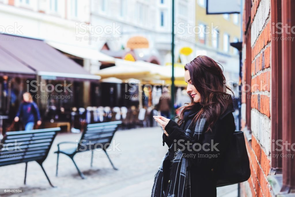 Photo of a business woman using smart phone, city business stock photo