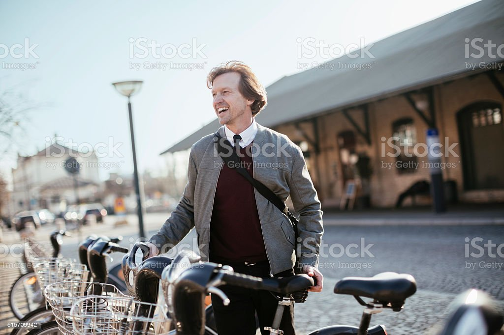 Photo of a businessman using bicycle shaing system stock photo
