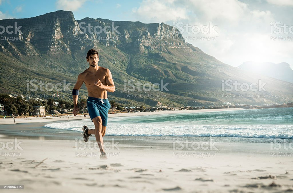 photo of a fit man running on the beach stock photo