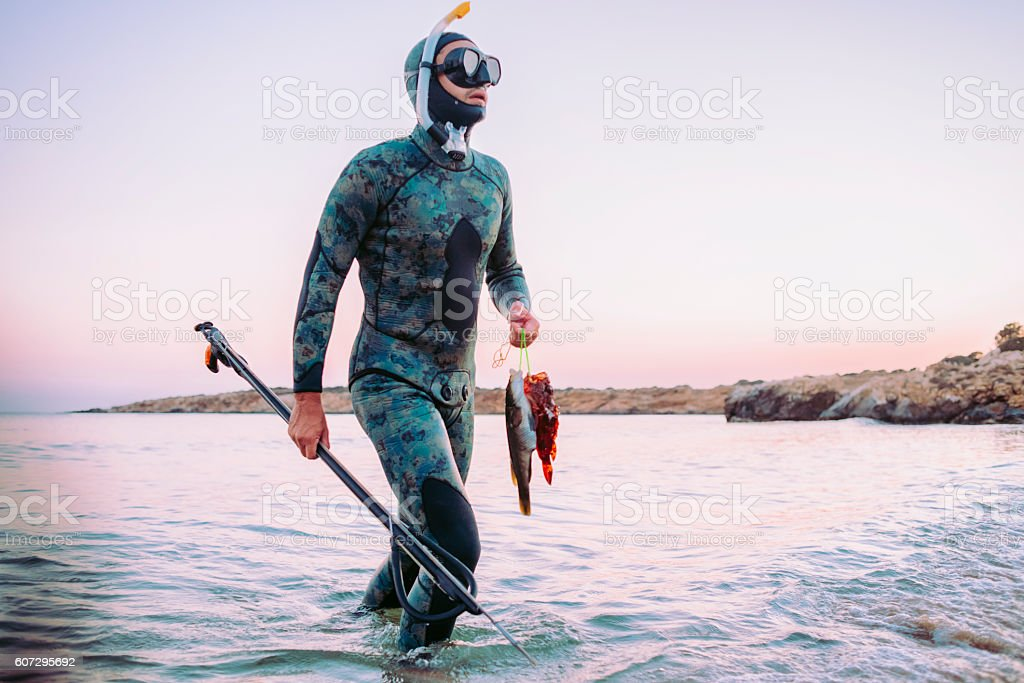 photo of a freediver coming back from spear fishing stock photo