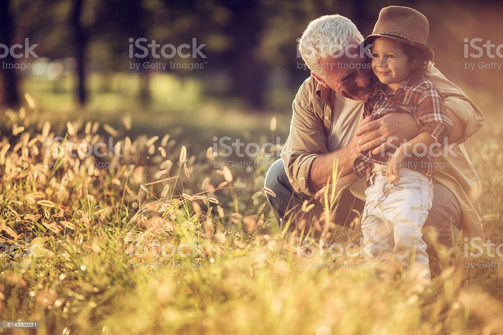 Photo of a grandfater and grandson in park stock photo