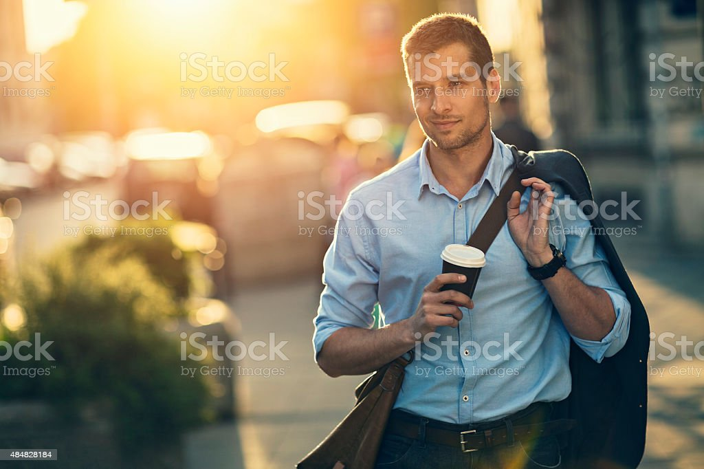 Photo of a handsome man having takeaway coffee in city stock photo