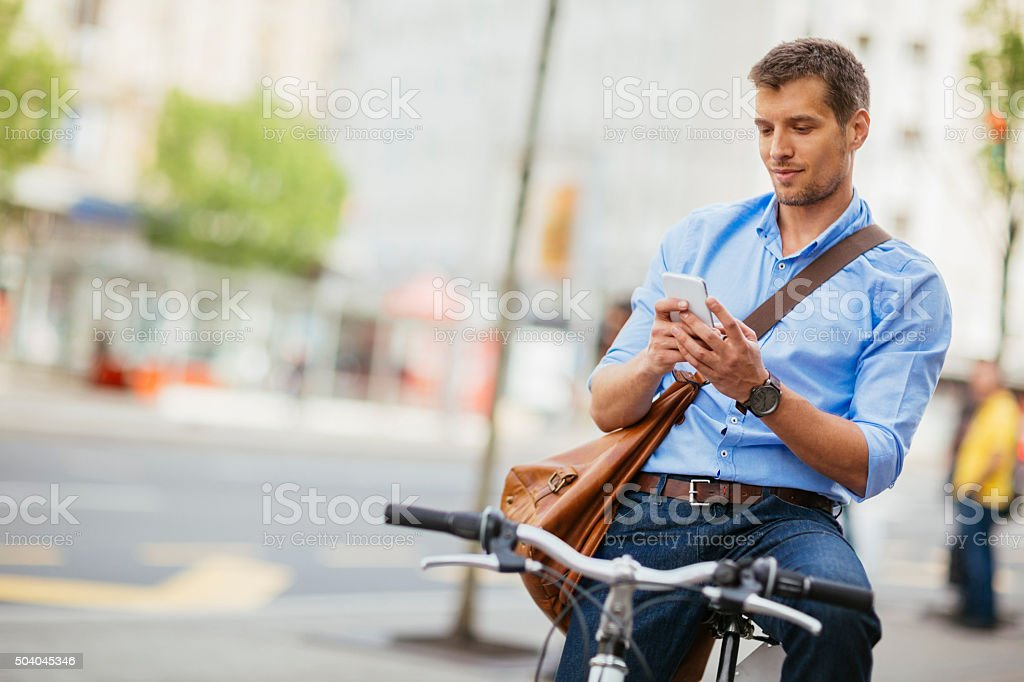 Photo of a handsome man holding smartphone in city stock photo
