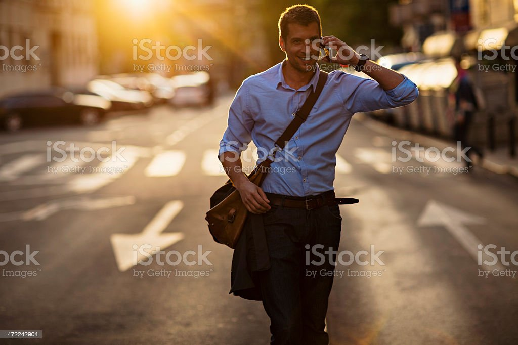 Photo of a handsome man in city speaking on phone stock photo