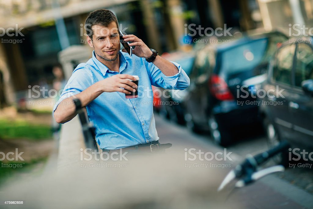 Photo of a handsome man in city speaking on smartphone stock photo