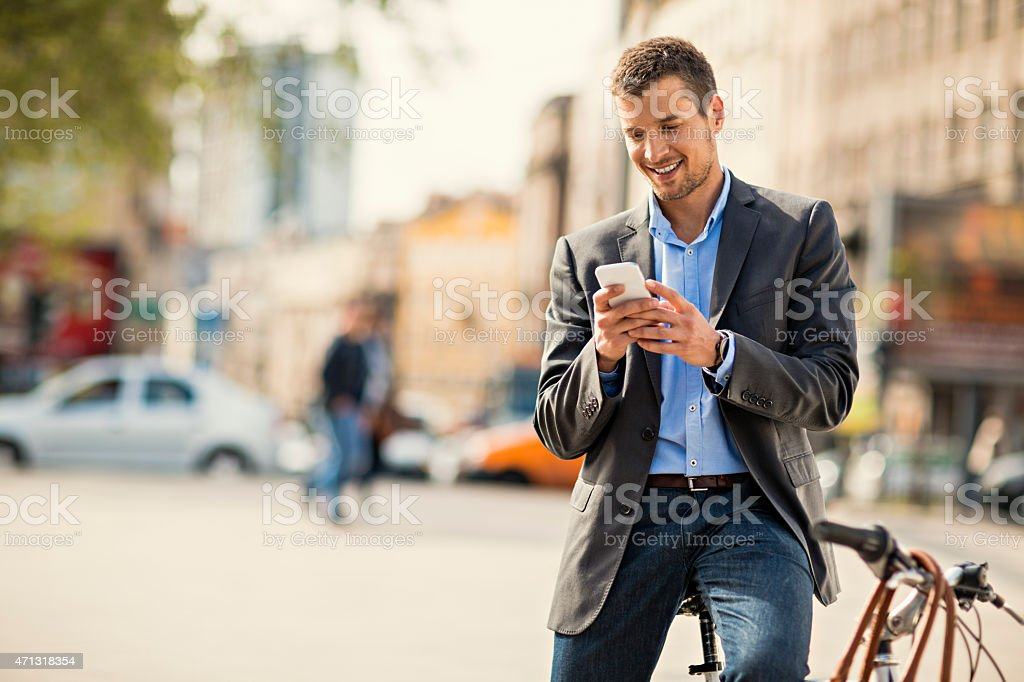 Photo of a handsome man with bike using smartphone stock photo