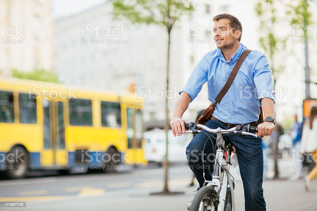 Photo of a handsome smiling man riding bike in city stock photo