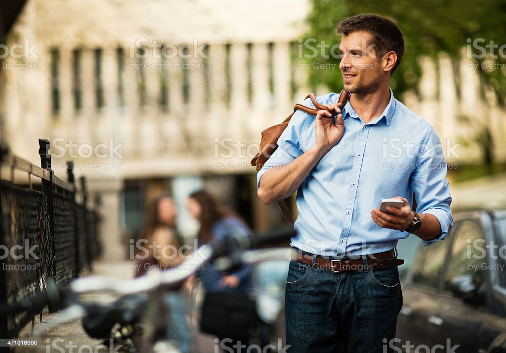 Photo of a handsome young man walking in city stock photo