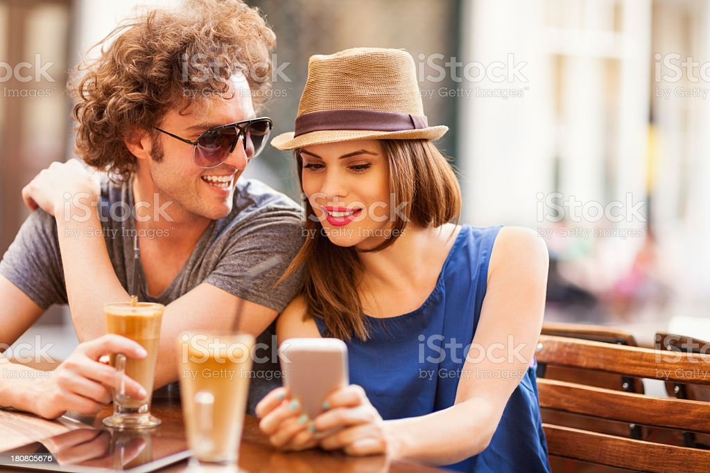 Photo of a happy couple looking at smartphone in cafe royalty-free stock photo