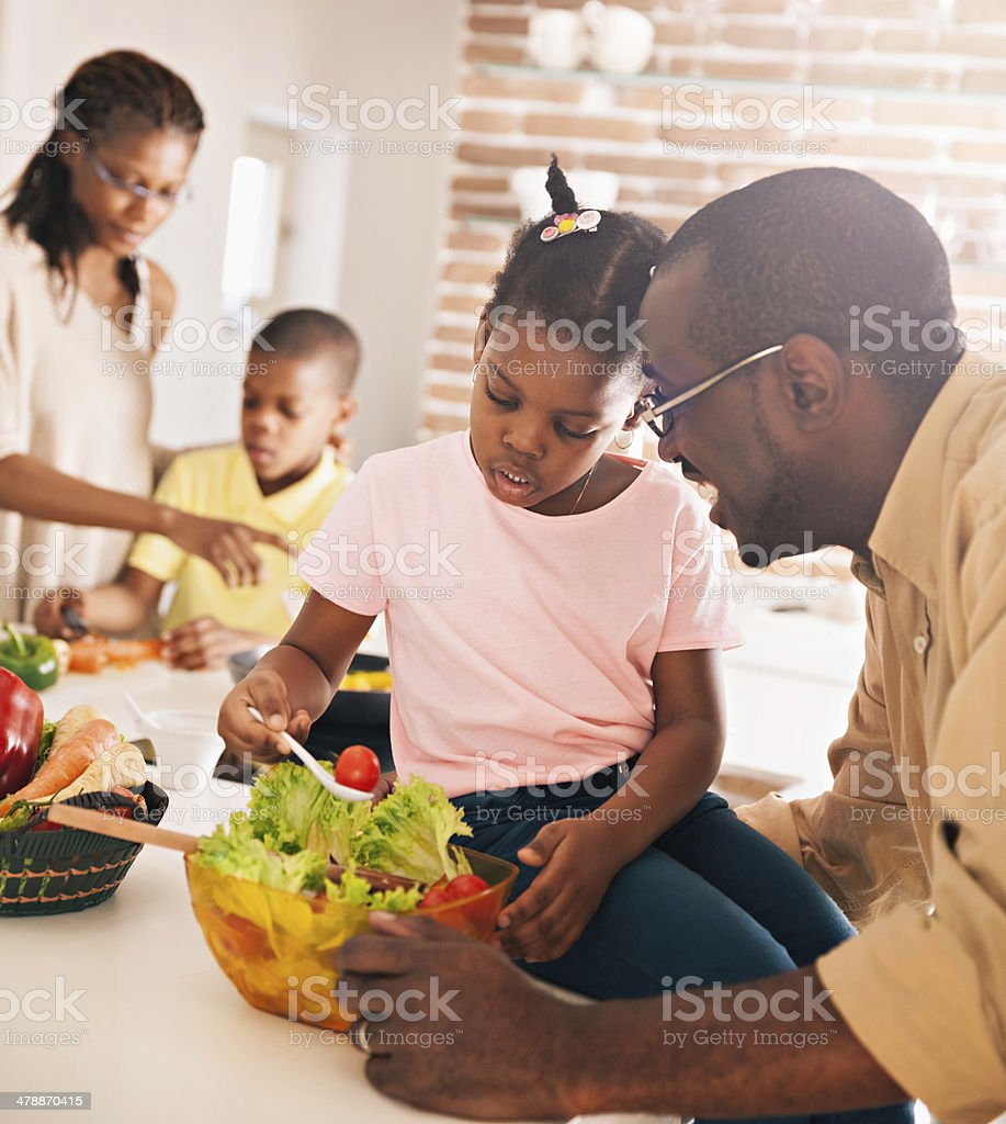 Photo of a happy family preparing food together stock photo