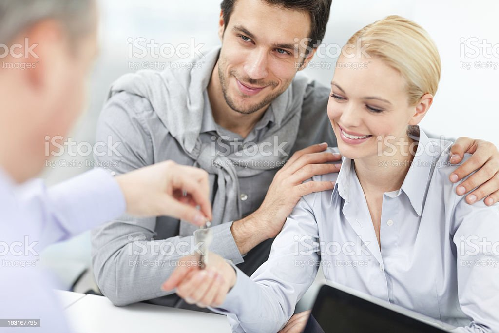 Photo of a happy young couple receiving new house keys royalty-free stock photo