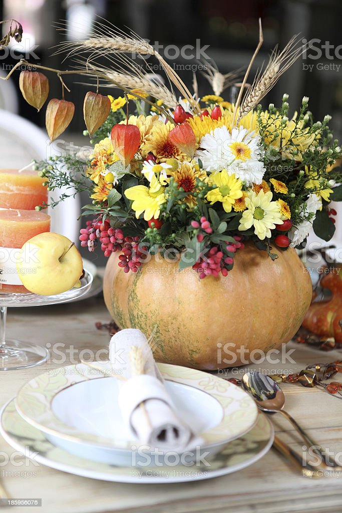 A photo of a harvest place setting with pumpkins stock photo