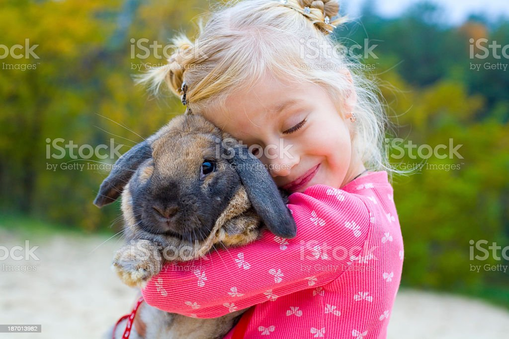 Photo of a little girl in pink clothes hugging a rabbit stock photo