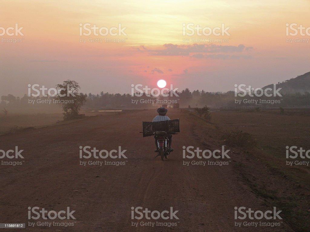 A photo of a man riding his bike at dawn royalty-free stock photo