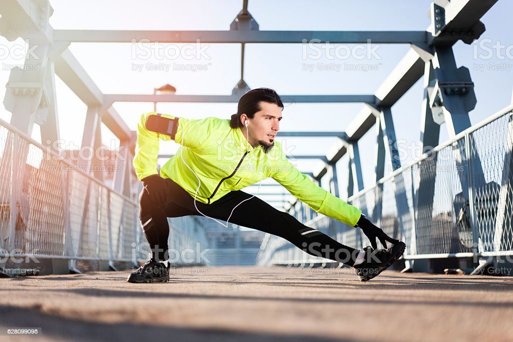 Photo of a man stretching in the morning before jogging royalty-free stock photo