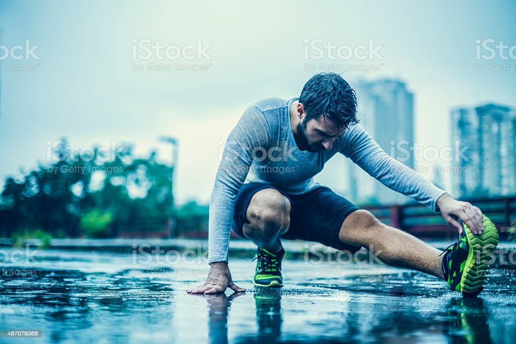 Close up of a man stretching in the rain