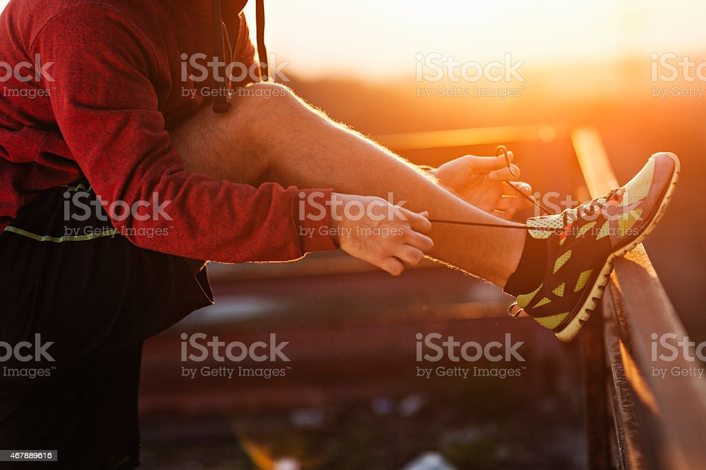 Photo of a man tying his shoe lace stock photo