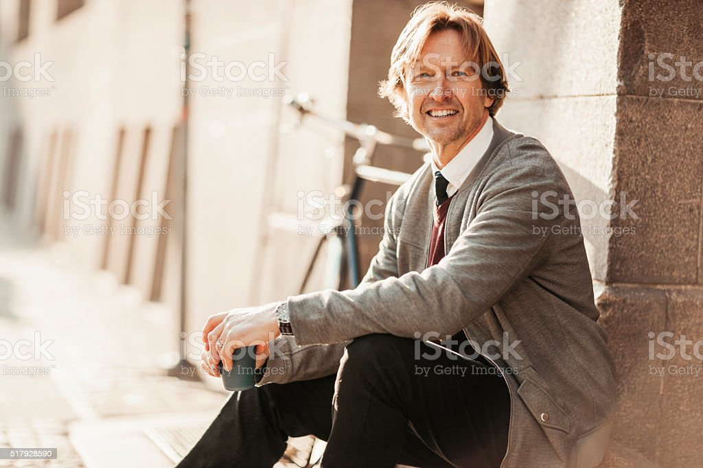 Photo of a mature man having coffee after work stock photo