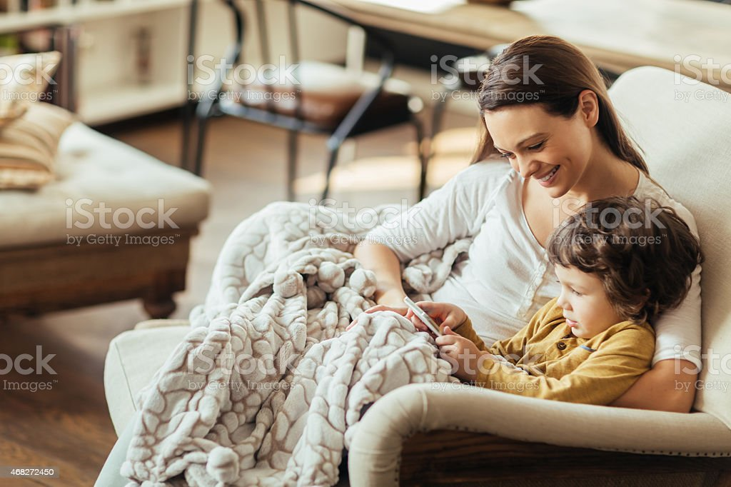 Photo of a mother and son looking at smartphone stock photo