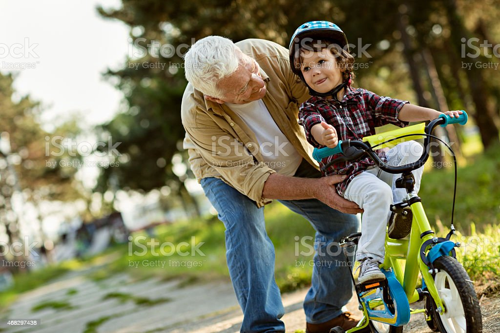 Photo of a proud grandfather teaching grandson to ride bike stock photo