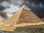 Photo of a pyramid in Giza showing stormy clouds above