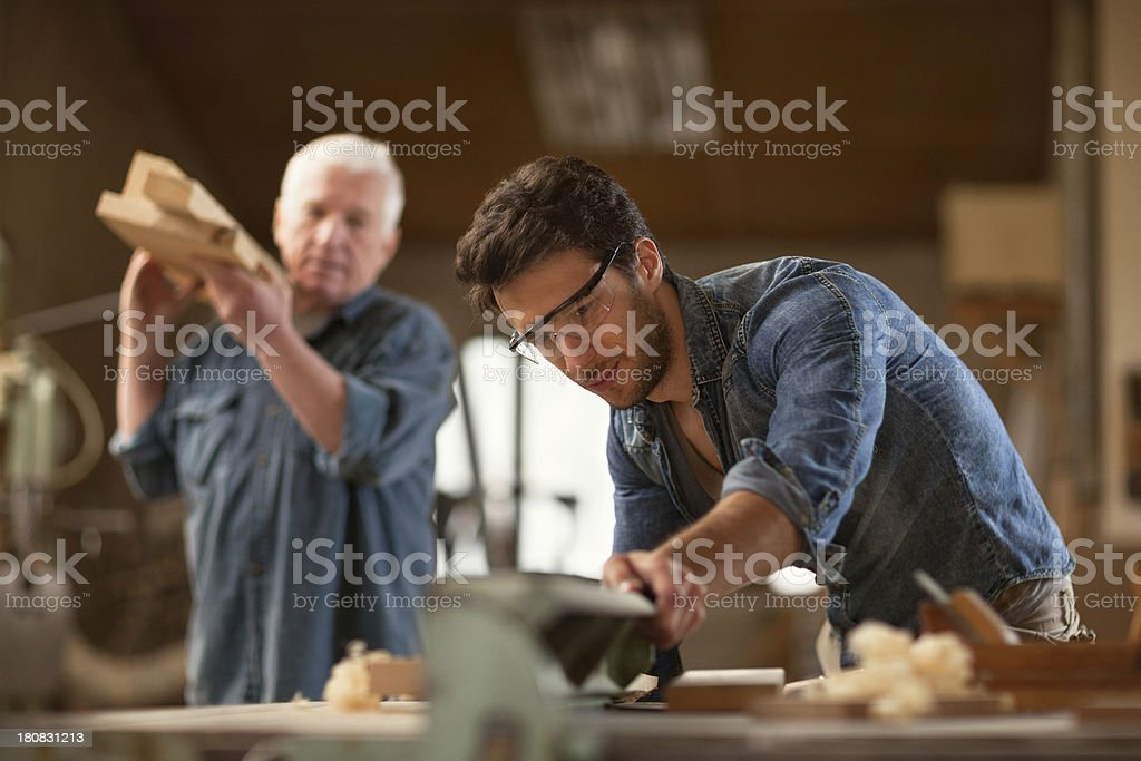 Photo of a senior carpenter and apprentice at work stock photo