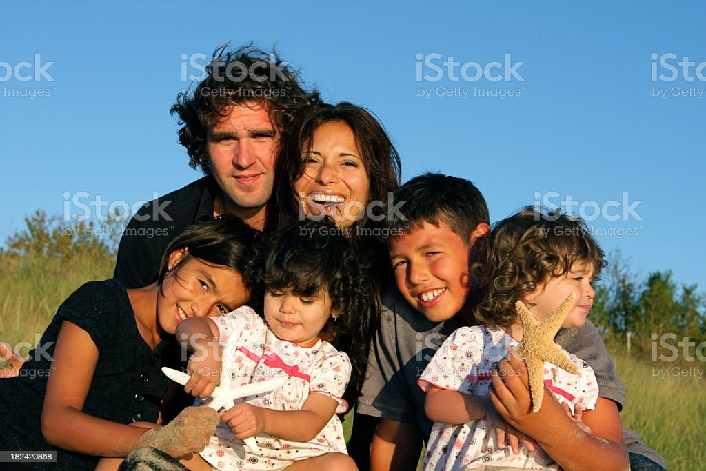 A photo of a smiling beautiful family at the beach stock photo