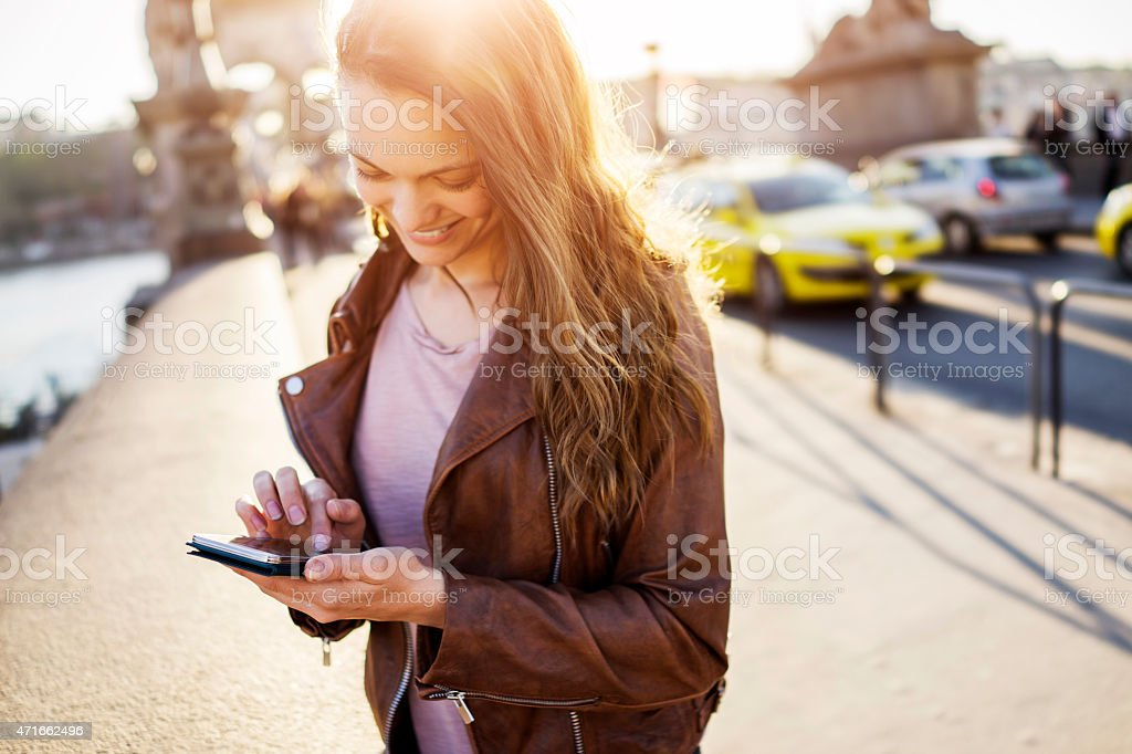 Photo of a woman standing with smartphone in capital city stock photo