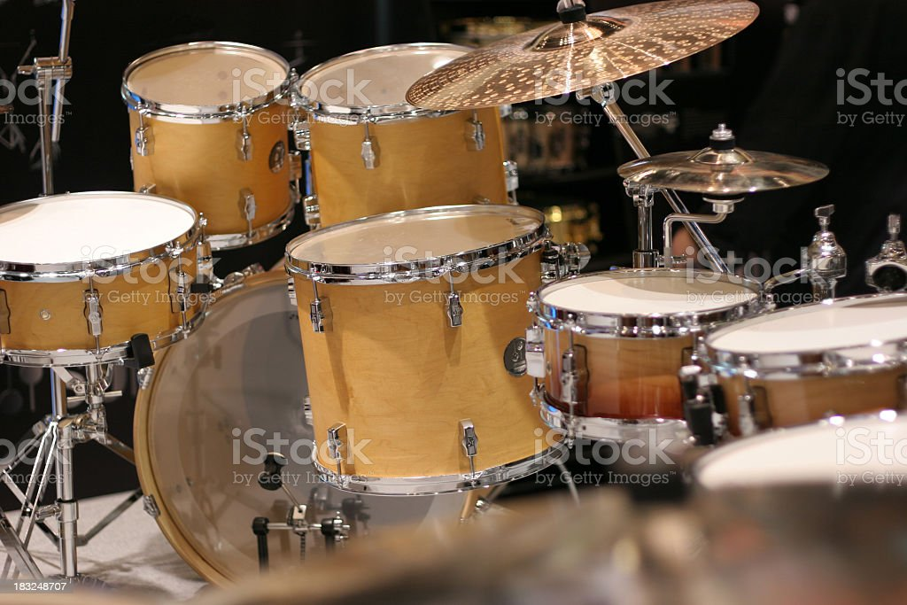 Photo of a yellow drum set on black stock photo
