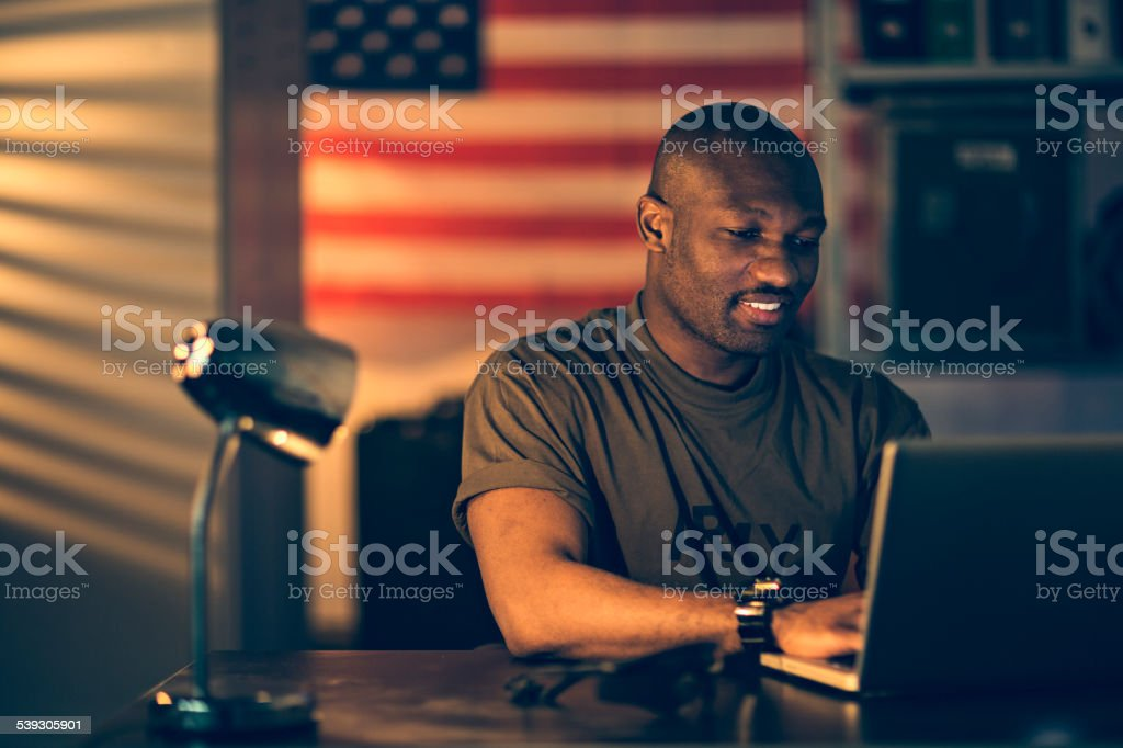 Photo of a young african american soldier using laptop stock photo