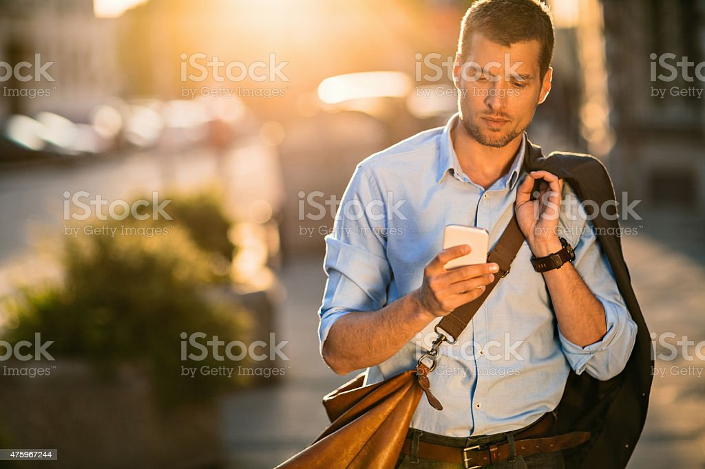 Photo of a young businessman using smart phone stock photo