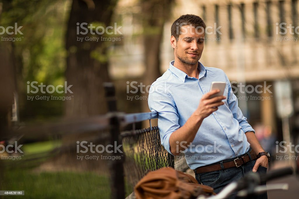 Photo of a young man in city checking his smartphone stock photo