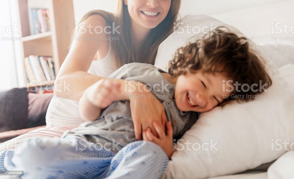 Photo of a young mother and son playing in pyjamas stock photo