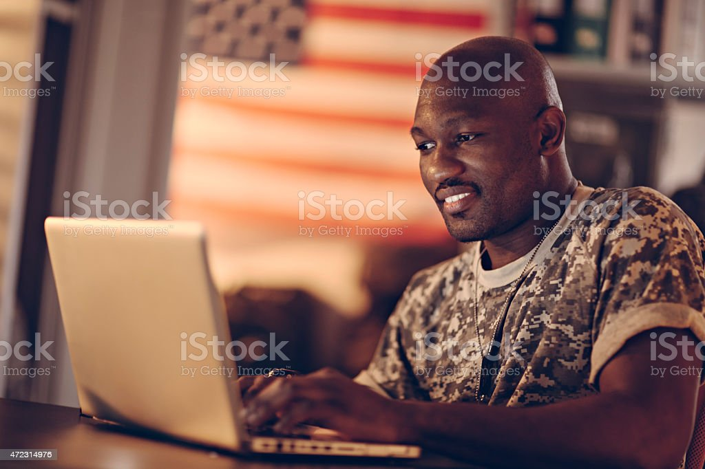 Photo of a young smiling soldier with laptop stock photo