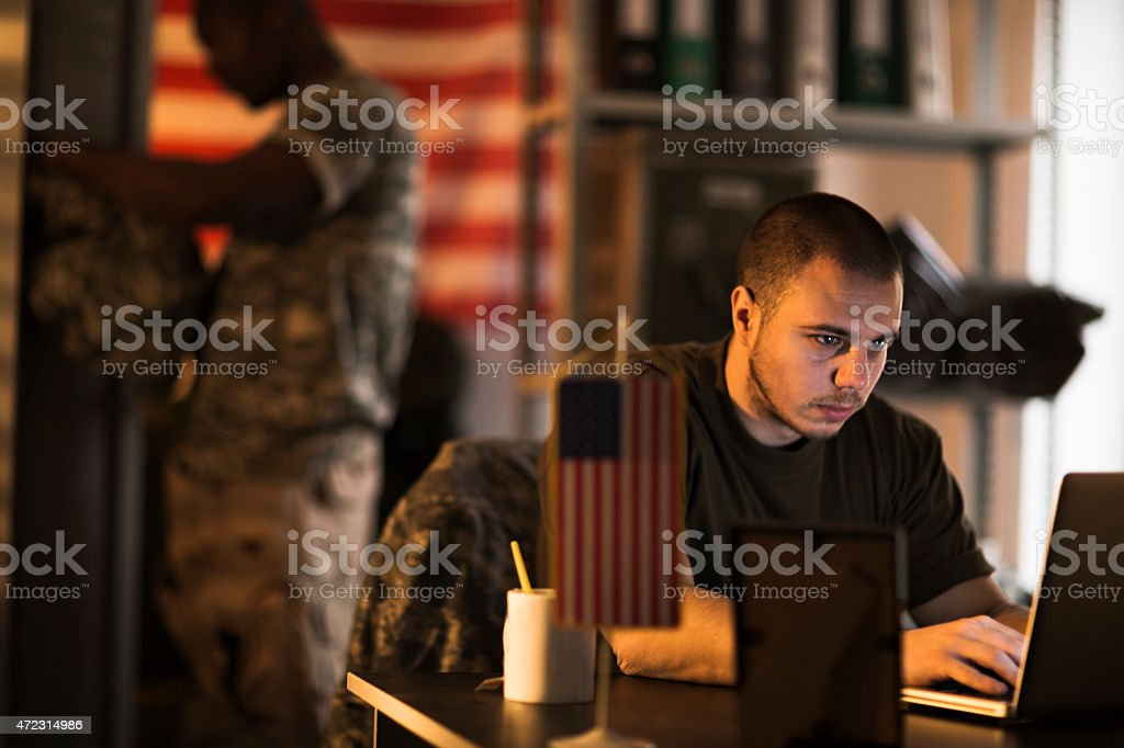 Photo of a young soldier bu his laptop stock photo
