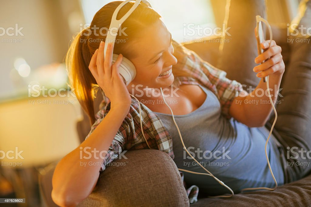 Photo of a young woman in sofa listening to music stock photo