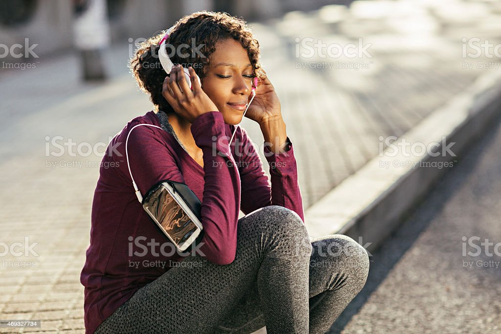 Photo of a young woman sitting down listening to music stock photo