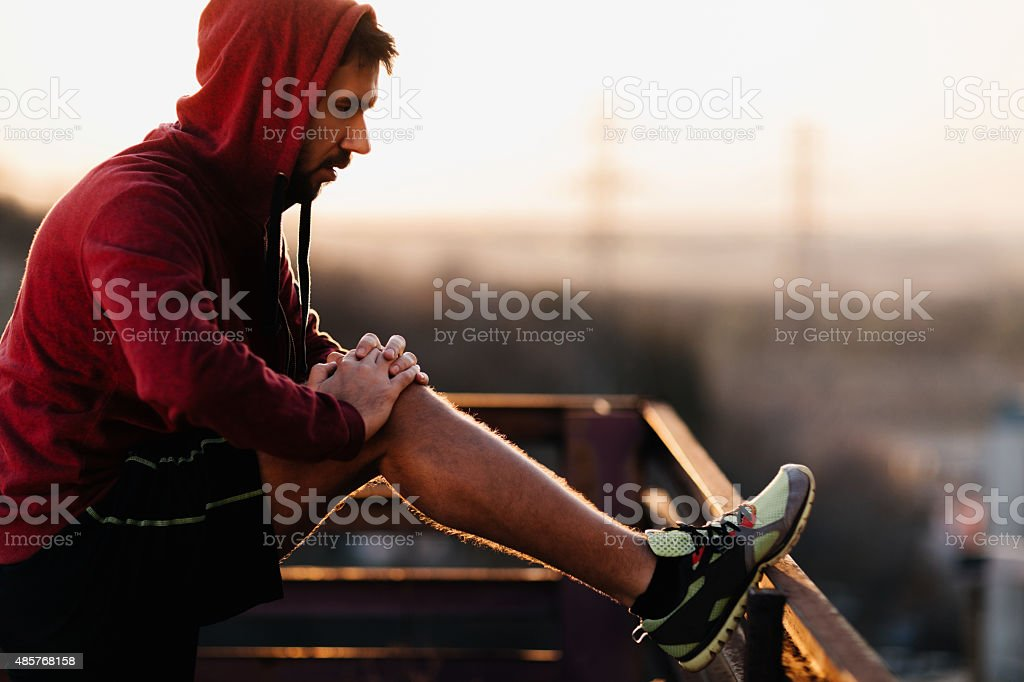 Photo of an athletic man stretching after exercise stock photo