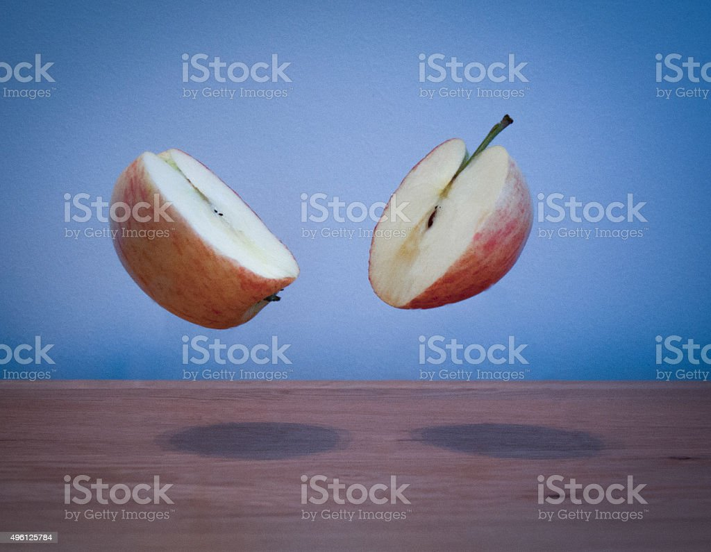 Photo of Apple sliced in half suspended in the air stock photo