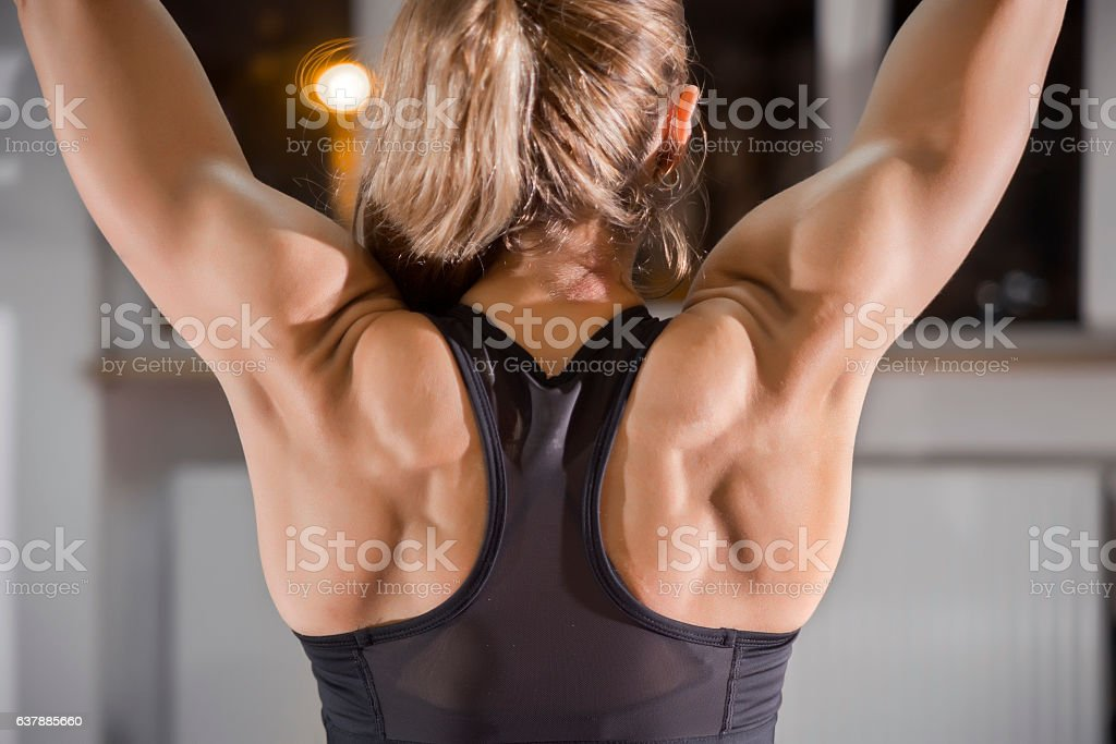 Photo of Athletic young woman showing muscles of the back stock photo