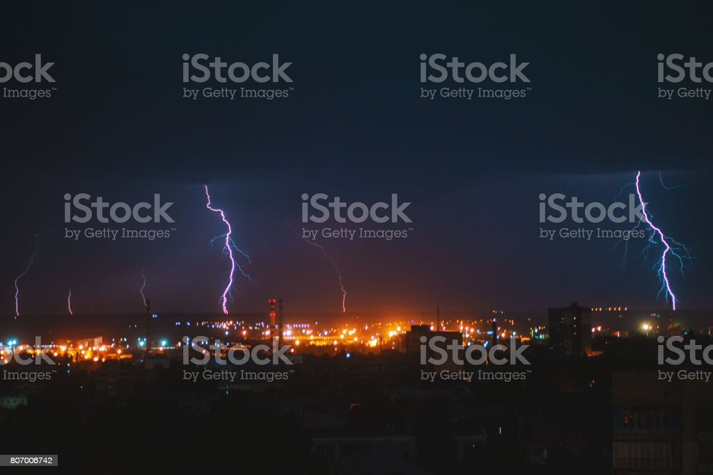 Photo of beautiful powerful lightning over big city, zipper and thunderstorm, abstract background, dark blue sky with bright electrical flash, thunder and thunderbolt, bad weather concept stock photo