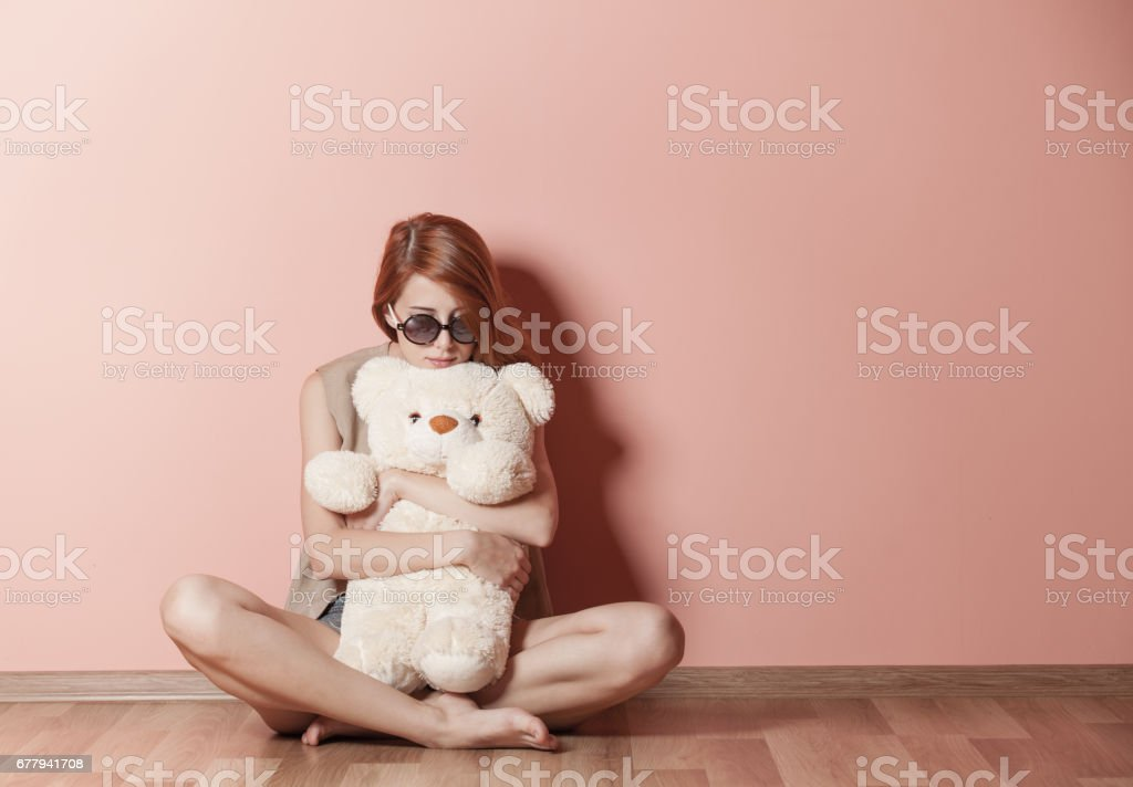 photo of beautiful young woman hugging teddy bear and sitting near...