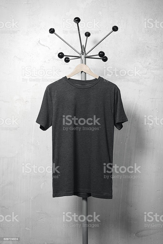 Photo of black blank tshirt hanging on the hanger. Vertical stock photo