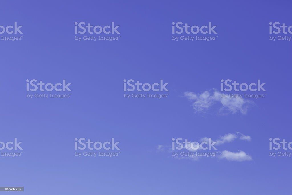 Photo of bright blue sky with small clouds forming on right stock photo