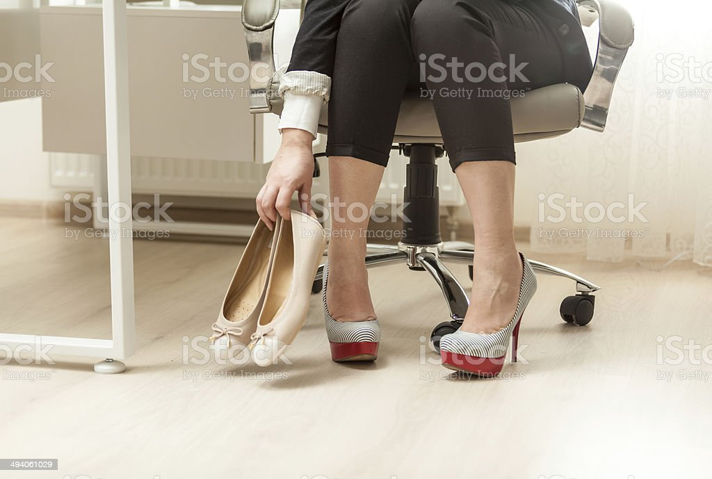photo of businesswoman changing shoes under table stock photo