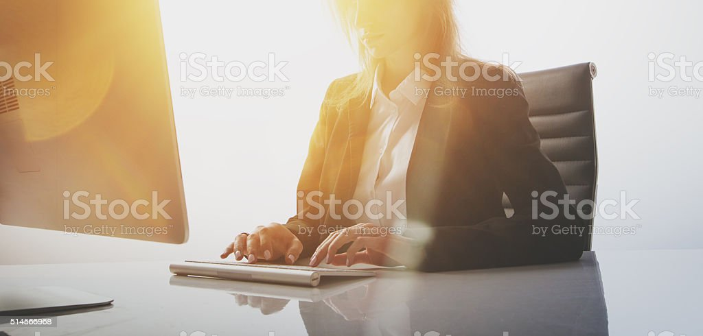 Photo of businesswoman working at table in modern, empty office stock photo