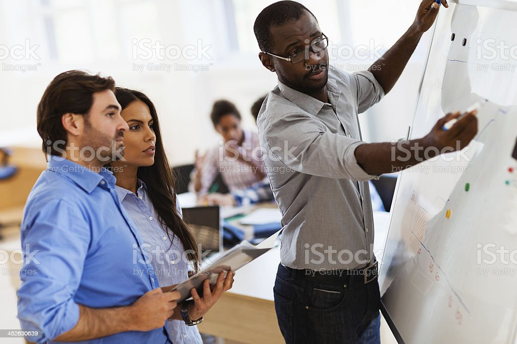 Photo of designers in office writing on white board stock photo